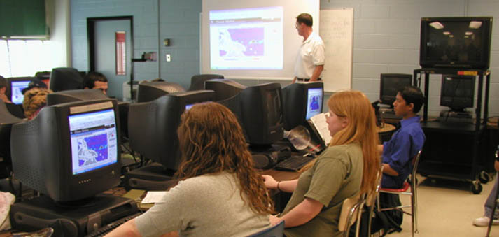 students in a classroom at walter johnson watching instructor david snyder describe a section of the website